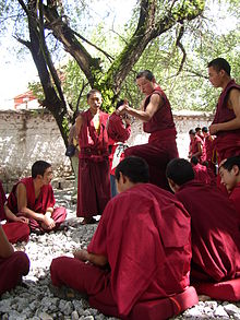 monks wearing crimson robes debating at Sera Monastery, Tibet