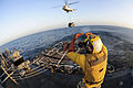 Defense.gov News Photo 111224-N-ED900-105 - U.S. Navy Petty Officer 3rd Class Victor Hernandez embarked upon the guided-missile destroyer USS Pinckney directs an SA330J Puma helicopter.jpg