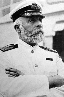 Photograph of a bearded man wearing a white captain's uniform with crossed arms