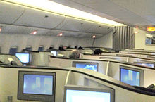 Airline business class cabin. Seats arranged with dividers, and display screens.