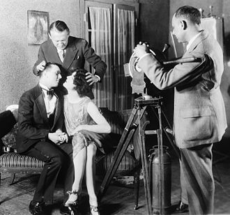 Edmund Goulding - Goulding helping position two actors for a kiss while making a film with the motion picture class at Columbia University in 1927.