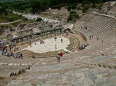 Το αρχαίο θέατρο της Έφέσου με ευδιάκριτα τα υποστηλώματα του προσκηνίου στο βάθος και τον εύριπο στην περιφέρεια της ορχήστρας