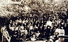 Large group of men in front of trees