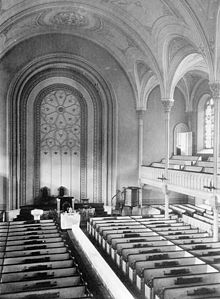 A black-and-white image of a church interior, seen from the gallery. The gallery and vaulted ceiling are supported by small columns.