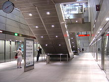 A square steel and glass room with some people waiting. In the middle are the backs of two escalators.