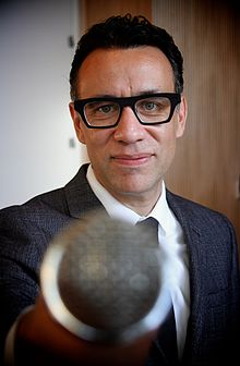 Armisen holding a microphone to the camera