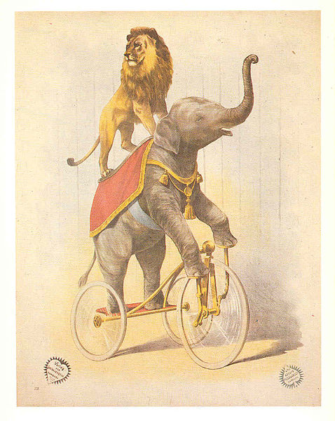 A lion rides on the back of an elephant pedaling a tricycle