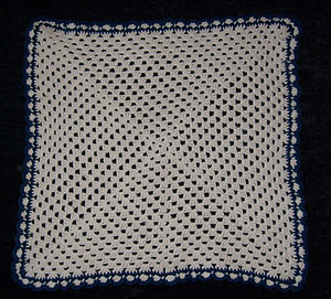 Shell stitch - A pet blanket constructed from a single granny square with a shell stitch border, enhanced in a contrasting color with half double crochet.
