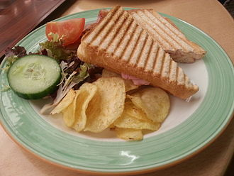 Ham and cheese sandwich - A grilled ham and cheese sandwich with a side of salad and crisps/chips