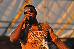 Gucci Mane performing in Williamsburg, Brooklyn on August 29, 2010. He is rapping into his microphone.