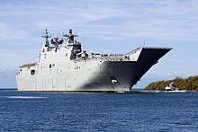 Ein graues Kriegsschiff, das nahe der Kuste segelt.