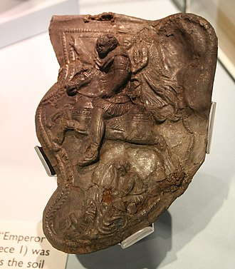 "Hallaton Helmet - The ""Emperor"" cheekpiece (no. 1), depicting a Roman emperor being crowned by Victory while trampling a barbarian under his horse's hooves"