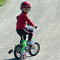 Helmeted boy on training wheels.jpg
