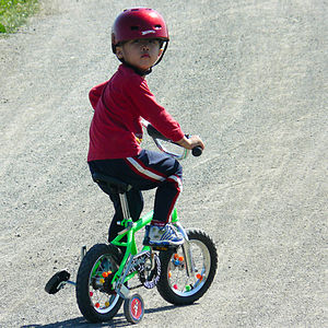 A boy riding a bicycle with training wheels