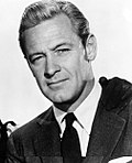 Black and white portrait of William Holden--a white man with light hair and small eyes, with a faint smile, wearing a suit, around 36 years of age--in 1954.
