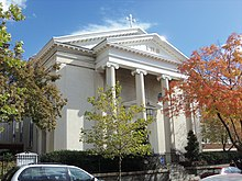 A white Neoclassical religious building in a residential neighborhood