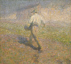 A peasant sowing seeds in an early foggy morning. A hayrack stands in the distance.