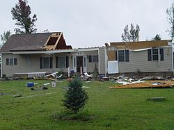 A partially destroyed house, with most of its roof and attic gone, is surrounded by scattered debris.