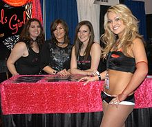 A photograph of four women, three sitting behind a table and one standing in front of it, all smiling at the viewer and wearing black