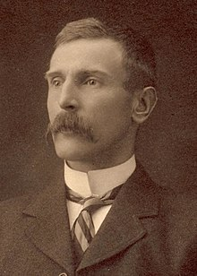 Head and shoulders portrait of a man with a moustache in a suit and tie with a high collar.