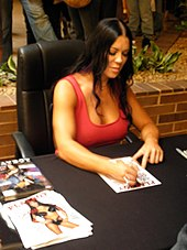 Chyna seated at event desk, signing