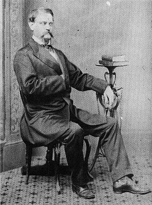 A mustachioed man sitting with his right hand in his waistcoat and his left arm resting on a bookstand