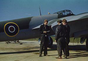 John de Havilland (pilot) - John de Havilland checking the flight log book with two fitters beside a Mosquito after a test flight, 1943