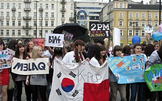 Korean Wave - K-pop fans outside the Korean Cultural Centre in Warsaw holding up a South Korean-Polish flag, as well as banners for Korean boybands MBLAQ, B1A4, and 2PM in 2011