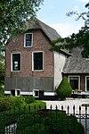 foto van Boerderij met langgerekt zomerhuis. Dwars woonhuis met opkamer, waarvan de puntgevel ontlastingsbogen van de oorspronkelijke vensters heeft