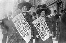 "Two women in early 20th century clothing wear sashes that read, ""Picket Ladies Tailer Strikers,"" while standing on a sidewalk in front of a building. A number of men stand on the sidewalk around them, some looking at the strikers, some facing away."