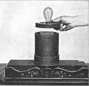 Inductive coupling - Example of inductive coupling, 1910. The bottom coil is connected to AC power. The alternating magnetic field through the top coil induces current in it which lights the lamp.