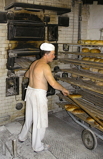 Baker - A traditional baker in Poland, removes fresh bread from an oven with a long wooden peel and places it on a cooling rack