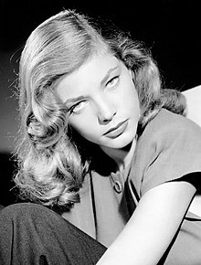 Lauren Bacall in black and white, her head tilted down with her eyes pointed up at the camera