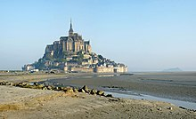 Mont Saint-Michel a hill monastery in a wetland, with the tide out