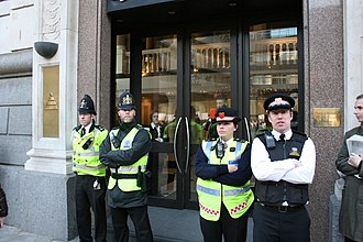 Police community support officer - Two PCSOs (right) of the City of London Police with two Police Constables keeping order during a protest outside The Church of Scientology in London. Note the distinctive unique red bands and badging on the PCSOs headgear.
