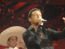 A man sings into a microphone. He is wearing a black shirt. Behind him, a man wearing a white sombrero plays on a silver trumpet.
