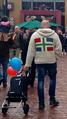 Man with a Groninger flag coat walking around at a Koningsdag market, Groningen (2019).png