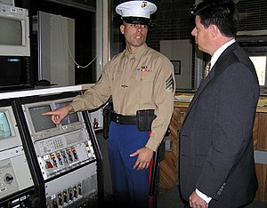 United States Marine Corps - A U.S. Marine security guard reviews a security system at a U.S. embassy in December 2004.