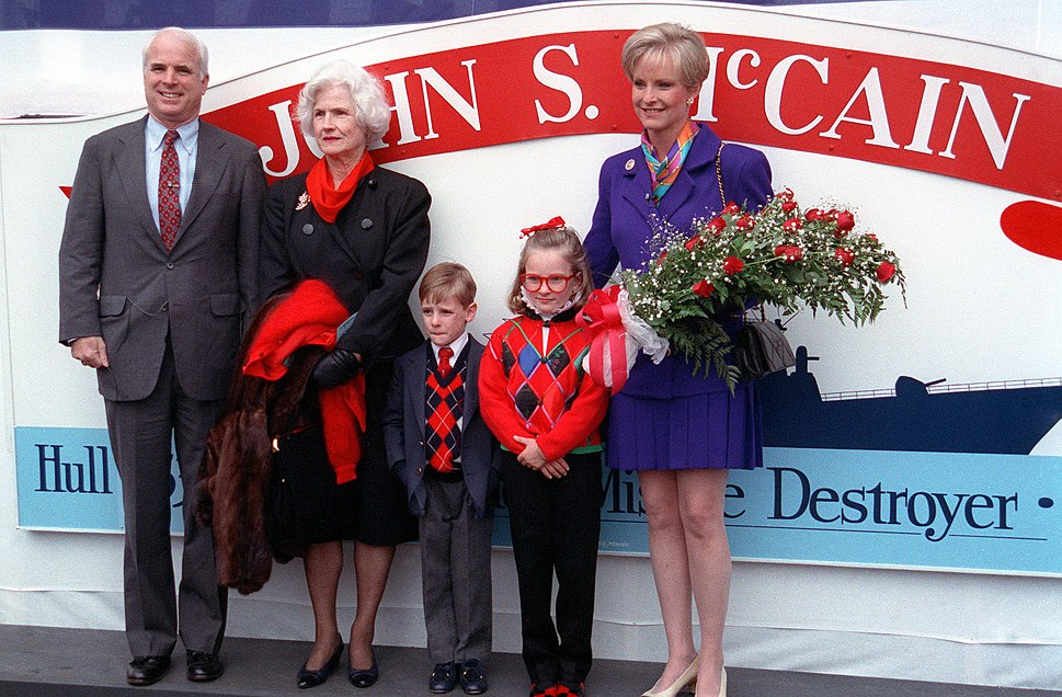 White-haired man, elderly white-haired woman, young boy, young girl, short-haired woman holding roses, all in front of sign showing a ship's silhouette