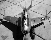 Black-and-white top view of egg-shaped aircraft, with a hook extended over top of canopy