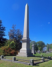 A tall marble obelisk against a clear blue sky with a low stone railing around it. There are smaller monuments, woods and a house in the background.