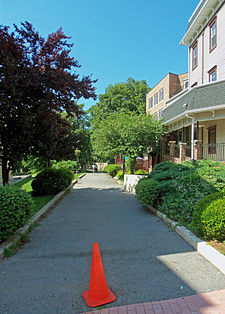 An asphalt path with an orange traffic cone at its beginning, in front of the camera. There are buildings and trees on both sides.