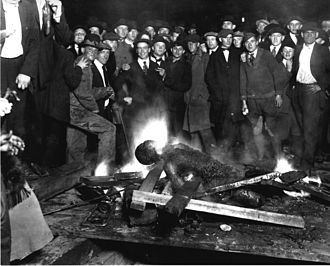 A group of white men pose for a 1919 photograph as they stand over the black victim Will Brown who had been lynched and had his body mutilated and burned during the Omaha race riot of 1919 in Omaha, Nebraska. Postcards and photographs of lynchings were popular souvenirs in the U.S. Omaha courthouse lynching.jpg