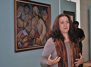 Salón de la Plástica Mexicana - Cecilia Santacruz discussing a painting by Alfredo Zalce in background at the Origen de un Acervo event