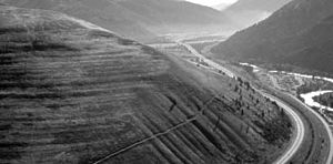 Lake Missoula - Wave-cut strandlines cut into the slope at left in photo. These cuts record former high-water lines, or shorelines. Gullies above the highway are the result of modern-day erosion. (NPS Photo)