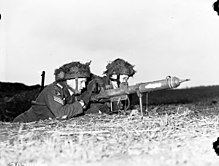 Two men in military uniform lie on a grassy bank, handling a tube shaped weapon