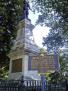 "A tall stone pedestal with a metallic figure atop it, with two large trees above it. The base is surrounded by an iron fence. In the front right is a blue marker with yellow type headed ""André Captured"", over smaller type describing that event."
