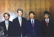 Four boys, in their late teens, wearing shirts, ties and blazers, standing in a line. The two on the left are white, while the two on the right are of oriental origin
