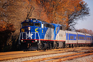 Blue and gray train with fall foliage