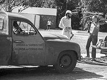 černobílá dobová fotografie přední části pick-upu Škoda 1201. Vpravo stojí muž a žena.